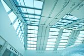 underside wide angled and perspective view to steel blue glass airport ceiling through high rise bui
