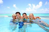 stock photo of bathing  - Family of four bathing in swimming pool - JPG