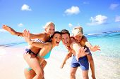 stock photo of blonde  - Family of four having fun at the beach - JPG