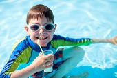 stock photo of all-inclusive  - Cute boy at all inclusive resort swimming pool sipping cocktail - JPG