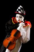Musical Pierrot holding an old violin against a black background