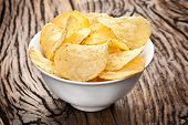 stock photo of crisps  - Potato chips in a bowl on a wooden table - JPG