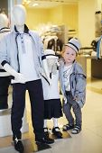 Pretty little boy poses near two mannequins in children clothing shop.