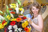 Beautiful smiling girl in elegant dress next to a bouquet of flowers