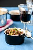 stock photo of boeuf  - boeuf bourguignon classic french beef stew on blue table with a glass of red wine - JPG