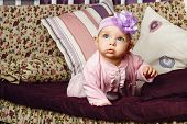 image of babygro  - Little girl with bow on her head sitting on couch - JPG