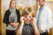 Portrait of boy trying eyeglasses with optometrist and mother standing in background at store