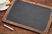 blank vintage slate blackboard with a chalk on wood table with a cup of coffee