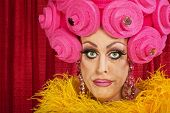 stock photo of frown  - Doubting drag queen with wig frowning in theater - JPG