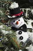 Happy Christmas snowman sitting in a snowy winter conifer fir tree