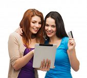 online shopping and technology concept - two smiling teenagers with tablet pc computer and credit card
