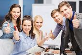 education, techology and internet concept - group of smiling students with computer monitor and tabl