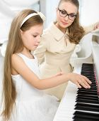 Master teaches little girl to play piano. Concept of music study and creative hobby