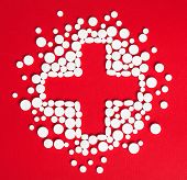 Close up of drugs placed in the form of cross, isolated on white. Concept of health care, medicine and quick recovery