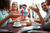 stock photo of gathering  - Portrait of happy teenage friends sitting and chatting in cafe - JPG