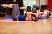 stock photo of rep  - Group of young cute women working out and doing some crunches at a gym - JPG