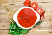 diet food : hot tomato vegetable soup with basil thyme and raw tomatoes in white round bowl over red