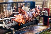 stock photo of spit-roast  - Pig turning over the coals at a pig roast