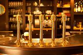 picture of spigot  - Luxury gold beer spigot at the brewery with a glass of beer - JPG