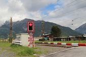 stock photo of railroad-sign  - Railroad crossing with a red warning sign in Austrian Alps - JPG
