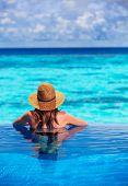 Rear view of young lady relaxing in the pool and enjoying view of beautiful seascape, refreshing in