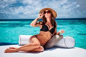 Sexy woman sitting on cozy white lounger on the beach, stylish model wearing fashionable hat and sunglasses, luxury summer vacation concept