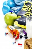 Different tools for sport and pills (Vitamins or Fitness Supplement) on white background - sport, health and diet concept