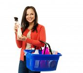 Beautiful cheerful brunette woman with basket full and bottle of cleanser