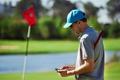 stock photo of gps  - modern golf man with smart phone taking score on mobile gps device next to green - JPG