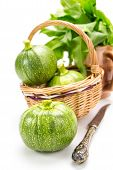 Three Round Zucchinis In Wicker Basket With Old Knife And Leafy Greens Isolated On White