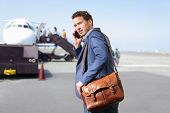 Airport business man on smartphone by plane. Young male professional hip businessman talking on smartphone boarding airplane going flying on business trip. Casual male wearing suit and laptop bag.