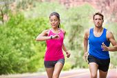 Runners - mixed multicultural couple training outside in nature. Fitness asian young smiling model c