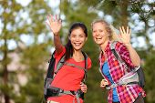 Hiking women waving hello with hands smiling at camera happy during hike trek outdoors in forest. Tw