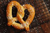 Freshly baked soft pretzel with generous sprinkling of coarse salt on wire cooling rack over rustic