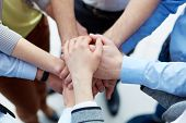 Business partners hands on top of each other symbolizing companionship