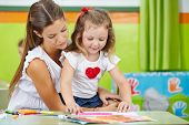 Girl doing arts and crafts with mother in nursery room