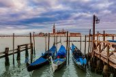 Gondolas tied on Grand Canal and San Giorgio Maggiore church on background under cloudy sky at evening in Venice, Italy.