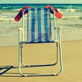 a deckchair with a pair of orange flip-flops on the beach, with a retro effect