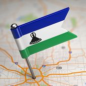 Lesotho Small Flag on a Map Background.