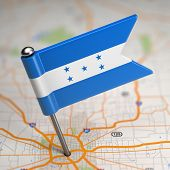 Honduras Small Flag on a Map Background.