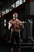 Mature Bodybuilder Exercising Biceps With Barbell
