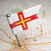 Guernsey Small Flag on a Map Background.