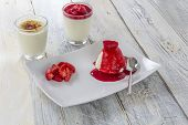 stock photo of panna  - two glasses of panna cotta with caramelized and red sauce topping and a plate with panna cotta and strawberry decoration on a wooden table - JPG
