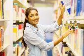happy female indian college student pulling a book off shelf in library