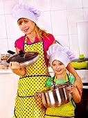 Children wearing hat and apron cooking at kitchen.