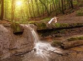 Woman practices yoga in nature the waterfall. parsvakonasana pose