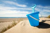 Childs bucket and spade or sand pail and shovel at the beach on a sunny summer day