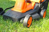 Closeup Of Electric Lawnmower On Green Grass