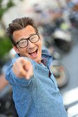 Cheerful guy with eyeglasses pointing at camera