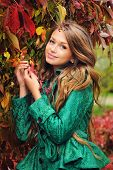 Portrait of a cute girl in green jacket under the autumn tree.